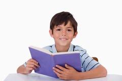 Lycklig pojkeläsning en boka Arkivbilder