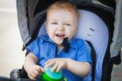 Lycklig pojkepojke i pram Arkivfoton