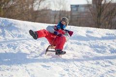 Lycklig pojkeridning på glidbanan på den snöig kullen royaltyfri fotografi