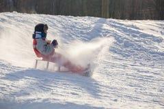 Lycklig pojkeridning på glidbanan på den snöig kullen arkivfoton