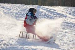 Lycklig pojkeridning på glidbanan på den snöig kullen royaltyfri foto