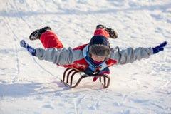 Lycklig pojkeridning på pulkan på den snöig kullen arkivbilder