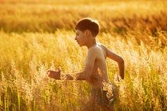 Lycklig pojkespring i ett fält Arkivbild