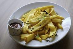 Lycklig pommes frites med solglasögon som kyler med hans stekte potatisvänner Arkivbild