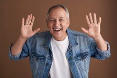 Lycklig positiv man som upp sätter två händer och att le fotografering för bildbyråer