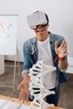 Lycklig positiv student som visar en DNAmodell Arkivbilder