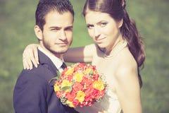 Lycklig precis gift brud och brudgum på bakgrund för grönt gräs Arkivfoto