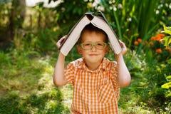 Lycklig pys för stående som rymmer en stor bok på hans första dag till skolan eller barnkammaren Utomhus tillbaka till skolabegre Arkivfoton