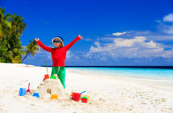 Lycklig pys med den byggda sandslotten på stranden Arkivbilder