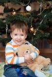 Lycklig pys med en nallebjörn i en julgran (3 år Arkivfoton