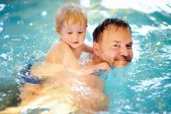 Lycklig pys med hans fader i simbassäng royaltyfria foton