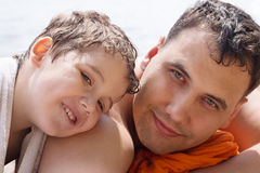 Lycklig pys med hans fader nära flodkust på su Royaltyfria Foton