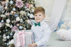 Lycklig pys med julg?van f?rtjust g?va f?r pojke Gullig unge som hem f?rbereder sig f?r xmas-ber?m Begreppet av arkivbilder