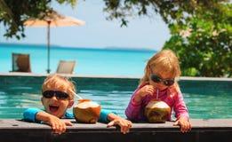 Lycklig pys och flicka som dricker kokosnötcoctailen på strandsemesterort royaltyfria foton
