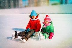 Lycklig pys och flicka som tillsammans åker skridskor arkivfoto