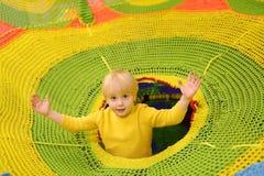 Lycklig pys som har gyckel i munterhet i lekmitt Barn som spelar på inomhus lekplats arkivbilder