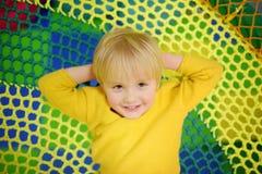 Lycklig pys som har gyckel i munterhet i lekmitt Barn som spelar på inomhus lekplats royaltyfria foton
