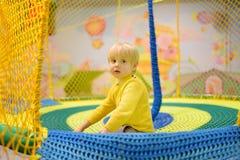 Lycklig pys som har gyckel i munterhet i lekmitt Barn som spelar på inomhus lekplats fotografering för bildbyråer