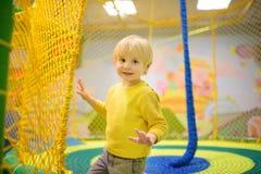 Lycklig pys som har gyckel i munterhet i lekmitt Barn som spelar på inomhus lekplats royaltyfri bild