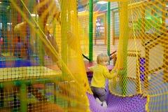 Lycklig pys som har gyckel i munterhet i lekmitt Barn som spelar på inomhus lekplats royaltyfri fotografi