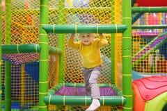 Lycklig pys som har gyckel i munterhet i lekmitt Barn som spelar på inomhus lekplats royaltyfri foto