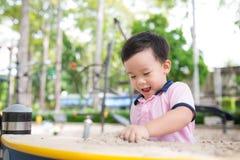 Lycklig pys som har gyckel på lekplatsen i sommar fotografering för bildbyråer