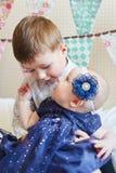 Lycklig pys som inomhus spelar med en behandla som ett barn, hans syster Royaltyfria Bilder