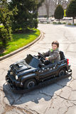 Lycklig pys som kör leksakbilen Fotografering för Bildbyråer