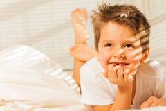 Lycklig pys som lägger och drömmer i hans säng arkivfoton