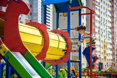 Lycklig pys som spelar i r?r eller tunnel p? den moderna lekplatsen lycklig din feriesommar f?r familj Lycklig och sund barndom arkivbilder