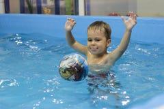 Lycklig pys som spelar med bollen i simbassängen arkivfoto