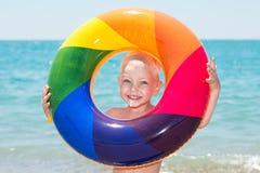 Lycklig pys som spelar med den färgrika uppblåsbara cirkeln på varm sommardag Barnvattenleksaker Barnlek i tropisk semesterort Fa royaltyfri fotografi