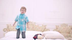 Lycklig pysbanhoppning på säng i sovrum gulligt litet barn eller litet barn som lyckligt hemma hoppar Lockigt behandla som ett ba lager videofilmer