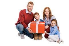 lycklig rödhårig manfamilj som rymmer den stora gåvaasken och ler på kameran royaltyfria foton