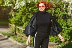 Lycklig rödhårig mankvinna i svart dräkt i sommar utomhus royaltyfria foton