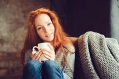 Lycklig rödhårig mankvinna som hemma kopplar av i hemtrevlig vinter- eller hösthelg med boken och koppen av varmt te som sitter i fotografering för bildbyråer