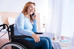 Lycklig rörelsehindrad kvinna som talar på telefonen Fotografering för Bildbyråer