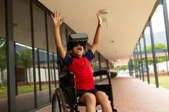 Lycklig rörelsehindrad skolpojke som använder virtuell verklighethörlurar med mikrofon i korridor royaltyfri bild