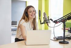 Lycklig radioutsändning för ung kvinna i en studio, slut upp royaltyfria foton