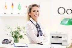 Lycklig receptionist som arbetar i hotell Arkivfoto