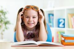 Lycklig rolig barnflicka i exponeringsglas som läser en bok Royaltyfria Foton