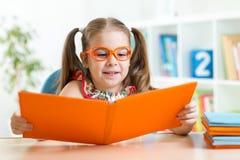 Lycklig rolig barnflicka i exponeringsglas som läser en bok Fotografering för Bildbyråer