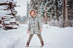 Lycklig rolig barnflicka på gå i snöig skog för vinter Royaltyfri Fotografi