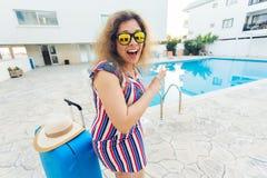 Lycklig rolig flicka på sommarferier på bakgrunden av pölen, den klädde randiga klänningen och solglasögon Arkivbilder