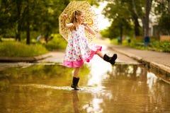 Lycklig rolig ungeflicka med paraplyet som hoppar på pölar i gummistöveler och i prickklänning royaltyfri foto
