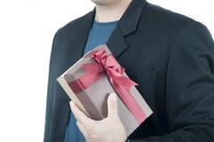 Lycklig romantisk grabb i den svarta dräkten som rymmer en brun närvarande gåvaask på vit bakgrund arkivfoton