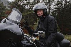 Lycklig ryttare och hans svarta motorcykel Royaltyfri Fotografi