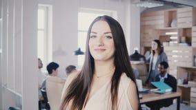 Lycklig säker europeisk ung kvinnlig chef med långt hår och fantastiska blåa ögon som ler på kameran i det moderna kontoret 4K arkivfilmer