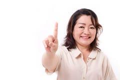 lycklig säker mitt åldras kvinna som pekar upp ett finger Royaltyfri Fotografi