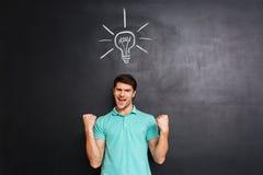Lycklig säker ung man som firar framgång och har en idé Arkivbild
